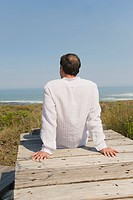 Rear view of a man sitting on a boardwalk