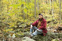 A man sitting on a rock in woodland