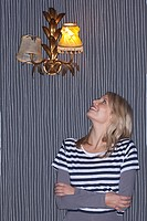 Young woman looking up at wall lamp
