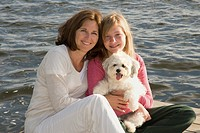 Mother and daughter on dock with dog, Lake of the Woods, Ontario, Canada