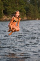 Young girl jumping into lake, Lake of the Woods, Ontario, Canada