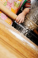 Stock photo of a four year old girl holding a rolling pin as flour is sprinkled onto the worksurface