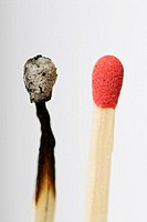 Stock photo of a live red match head next to an old burnt out match head  Conceptual image to illustrate before, after - old, new - change, dare to be...