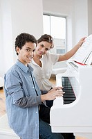 Woman giving piano lesson to boy