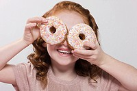 Girl holding doughnuts to her eyes