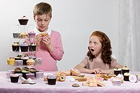 Boy and girl with table of cakes
