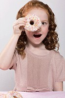 Girl holding a doughnut to her eye