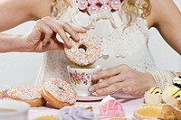 Woman with doughnut and cup of tea