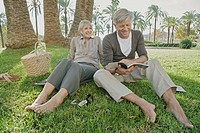Barefoot man and woman relaxing on grass