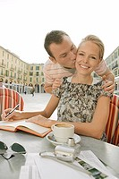 Man kissing woman sitting at cafe table