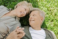 Man and woman holding hands laying on grass