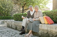 Man and woman sitting on wall with shopping bags