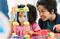African American girl playing with toy while mother watches