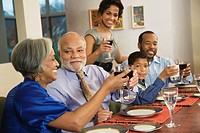 African American family toasting with wine at dining table