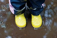 rainy weather - yellow gumboots in a puddle