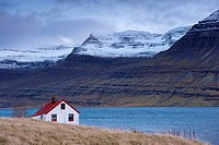 Red_roofed house and snow_capped mountains in Reydarfjordur fjord, East Fjords, Iceland, Polar Regions