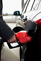 close-up of a hand refilling the car with a gas pump