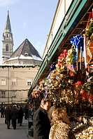 Stall selling Christmas decorations with towers of Franziskanerkirche churchbehind, Historical Salzburg Christkindlmarkt Christmas market, Domplatz, S...