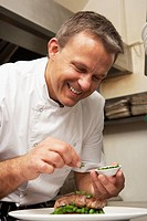 Chef Adding Seasoning To Dish In Restaurant Kitchen