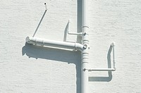 White drainpipes against white wall