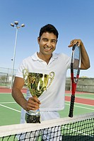 Man on tennis court Holding Trophy portrait