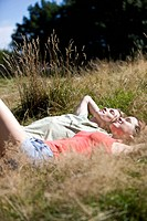 A young couple lying on the grass, relaxing