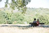 A young couple sitting on a bench in a park