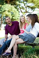 Four young people sitting on a bench, talking