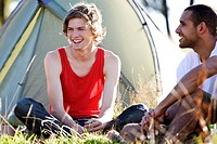 Two young men sitting in front of a tent, laughing