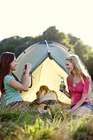 Three young women camping, one taking a photo
