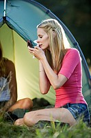 Two young women camping, one wiping her face