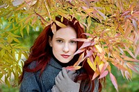 A young woman standing under a tree in autumn time (thumbnail)