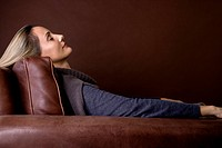 A mid adult woman resting in an armchair