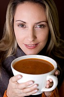 A mid adult woman holding a cup of soup (thumbnail)