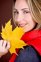A mid adult woman holding an autumn leaf, smiling