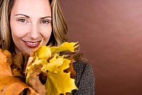 A mid adult woman holding a handful of autumn leaves