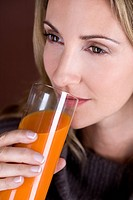 A mid adult woman drinking a glass of fruit/carrot juice (thumbnail)