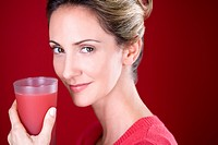 A mid adult woman holding a glass of fruit juice