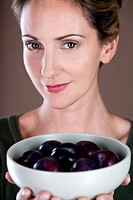 A mid adult woman holding a bowl of plums