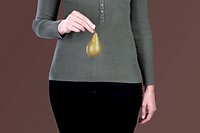 A woman holding a pear in front of her hips