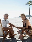 Senior couple on sunloungers on tropical beach