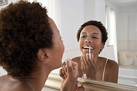 Woman applying lip gloss in mirror at home