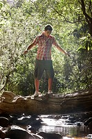 Teenage boy 16_17 years walking tree trunk above stream