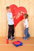 Geschwister malen ein Herz auf Holzbretter, Studio, Zuerich, Switzerland