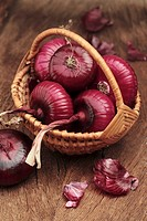 Several red onions in a wicker basket