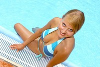 Blonde woman relaxing by the pool in the summer holidays
