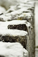 Fresh white snow on a stone wall.