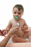 Female hand holding stethoscope to baby boy