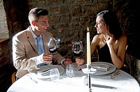 Couple sitting at restaurant table toasting with red wine