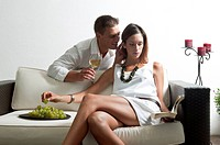 Young man leaning on couch with white wine whispering in young woman's ear reading book and eating grapes